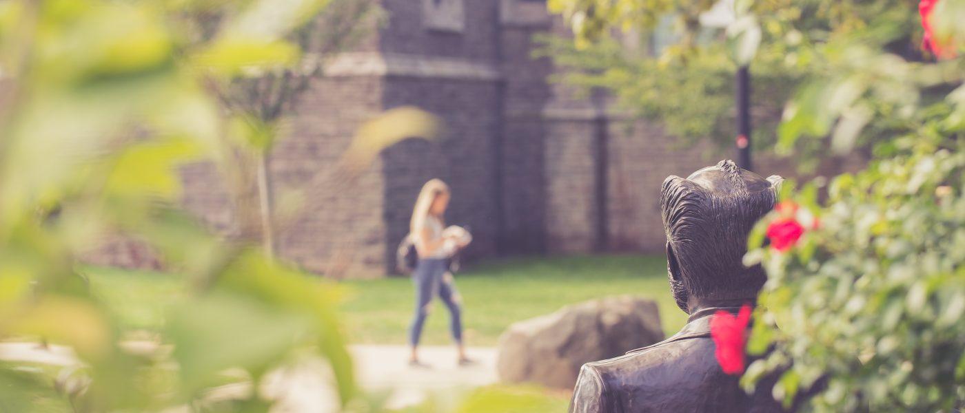 Student Walking Past Senator William McMaster Statue